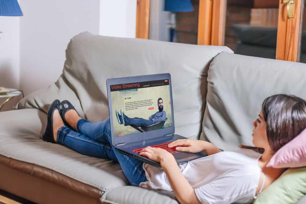 une femme est assise sur le canapé et un bouton sur l'ordinateur portable