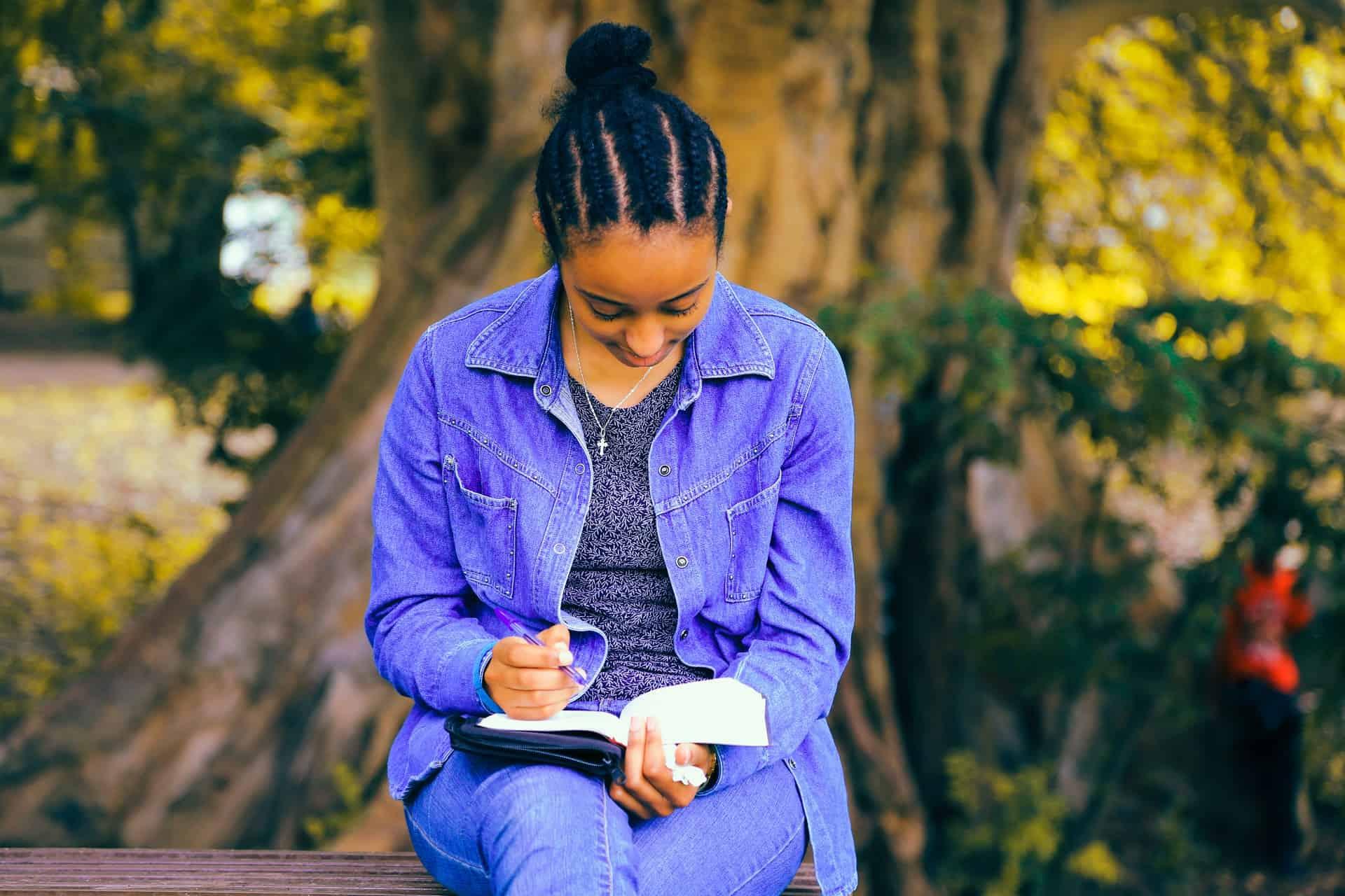 une femme est assise sur un banc et écrit