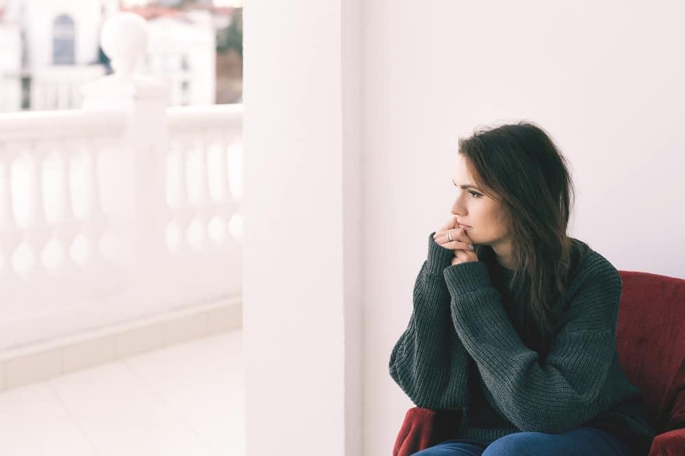 une femme imaginaire est assise dans un fauteuil et regarde ailleurs