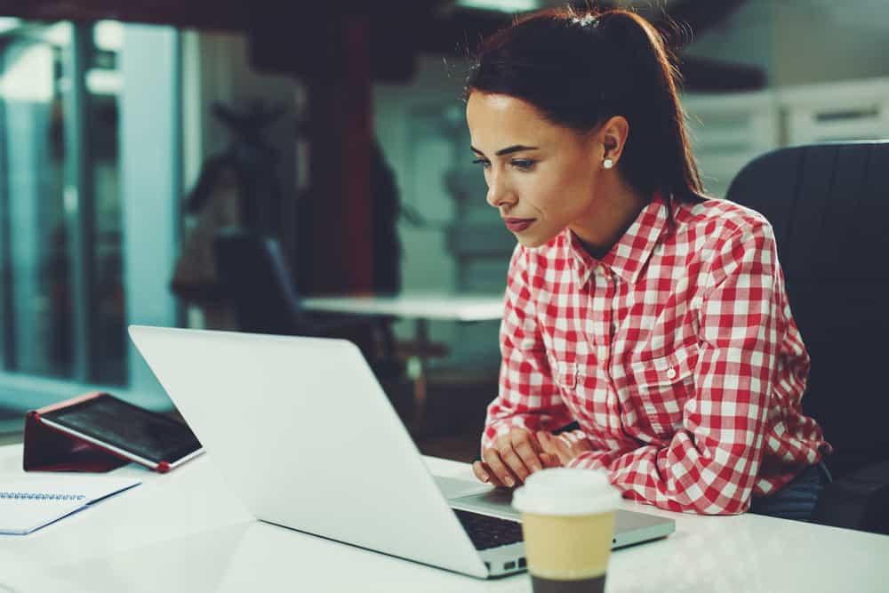 une femme imaginaire est assise devant un ordinateur portable et travaille