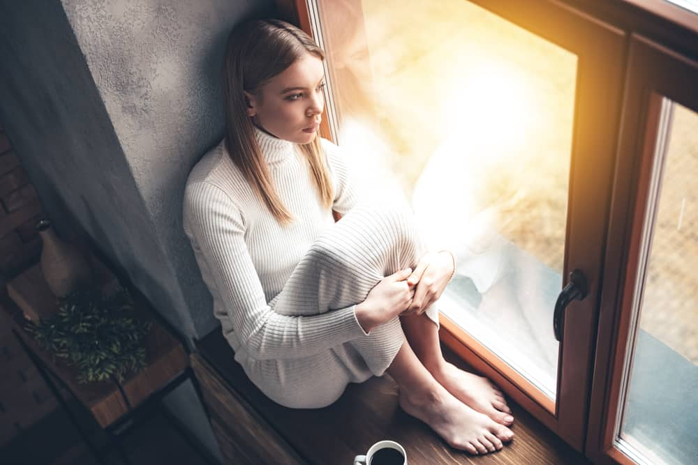 une femme imaginaire est assise près de la fenêtre avec une tasse de café et pense