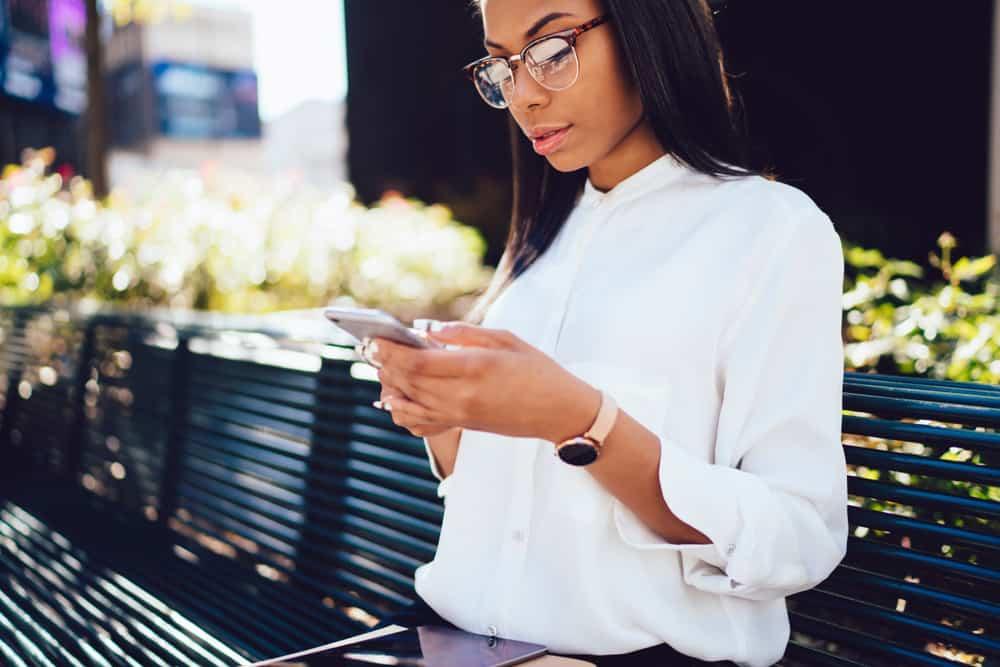 une femme noire sérieuse se tient dehors et envoie des SMS