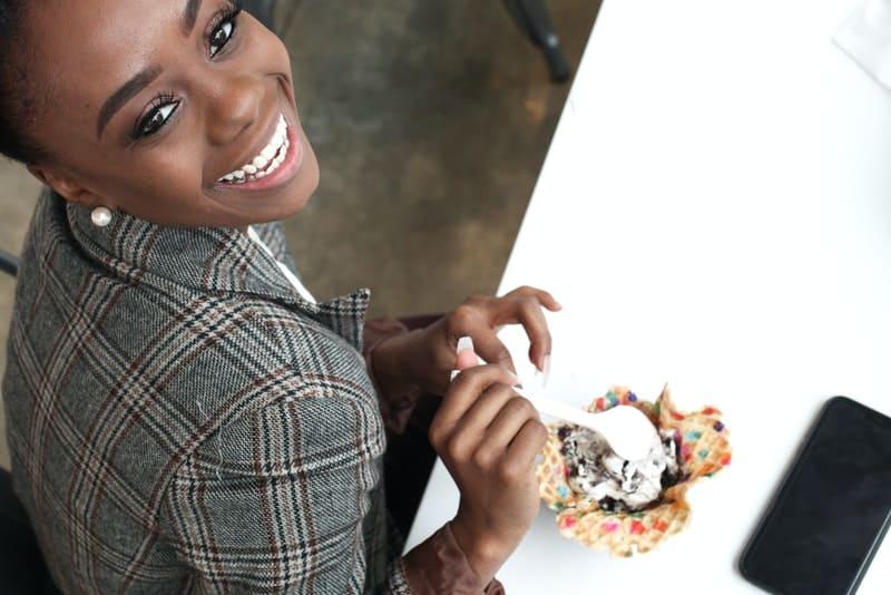 une femme noire souriante mange de la glace