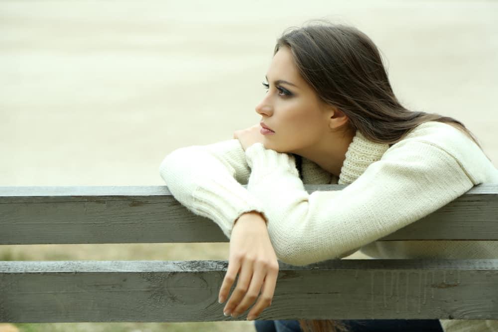une femme pensive est assise sur une chaise