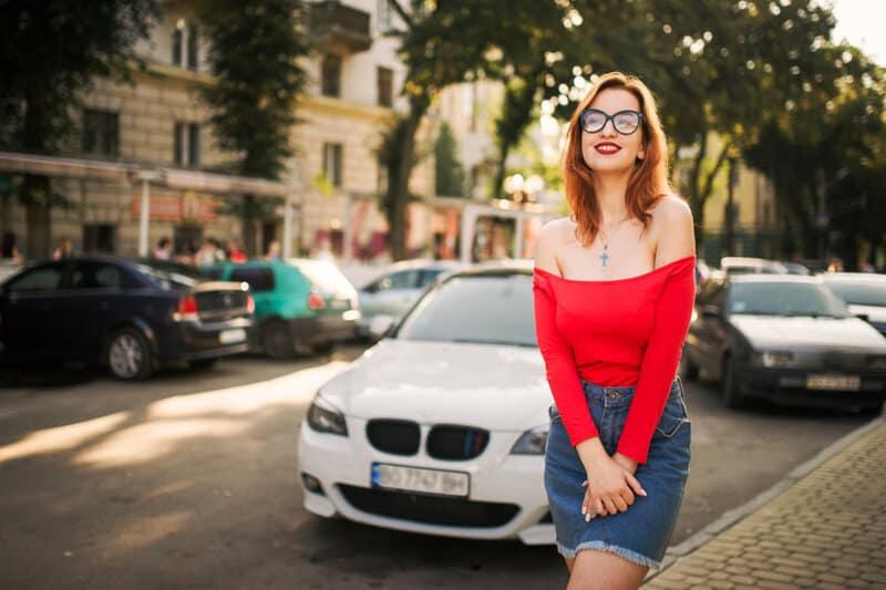 une femme se tient dans la rue avec des lunettes sur la tête