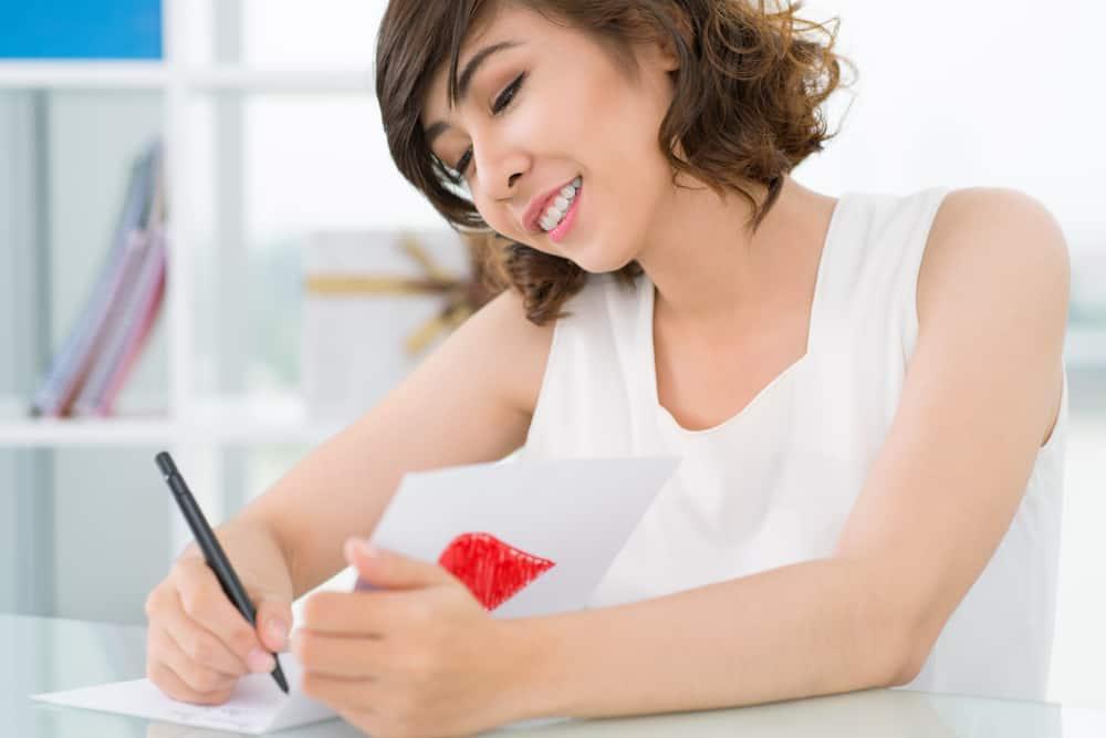 une femme souriante amoureuse écrit une lettre