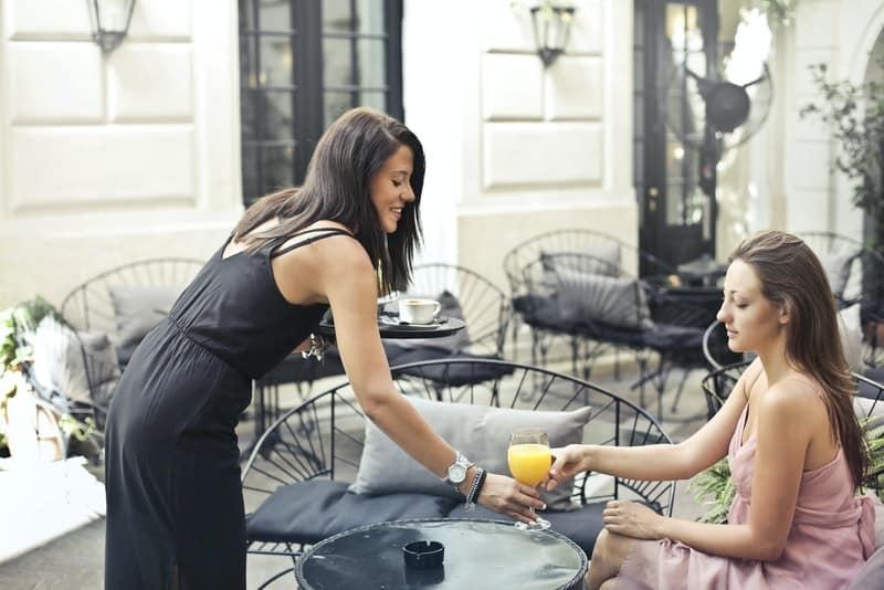 une femme souriante apporte du jus à une autre femme