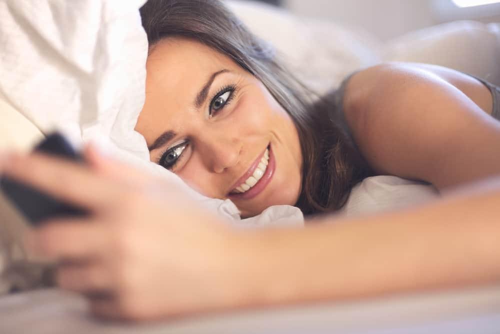 une femme souriante heureuse est allongée dans son lit et à l'aide d'un smartphone