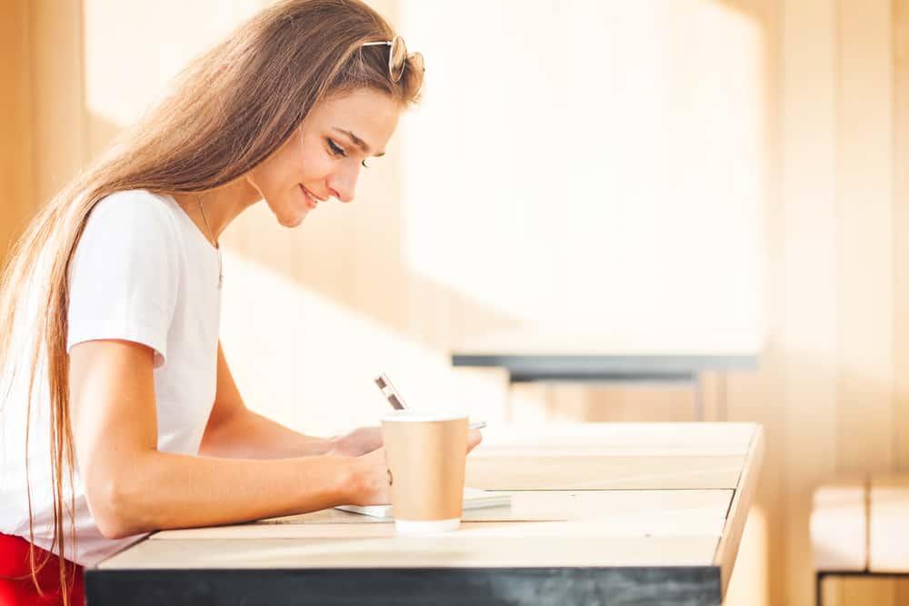 une femme souriante s'assied et écrit quelque chose