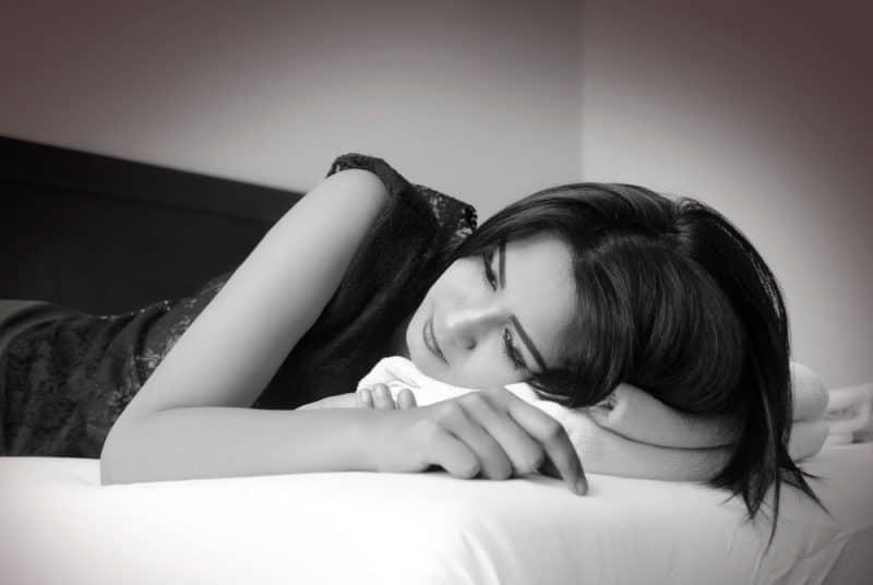 une femme triste allongée sur le lit