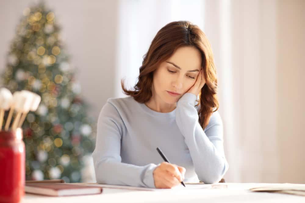 une femme triste est assise à une table et écrit quelque chose