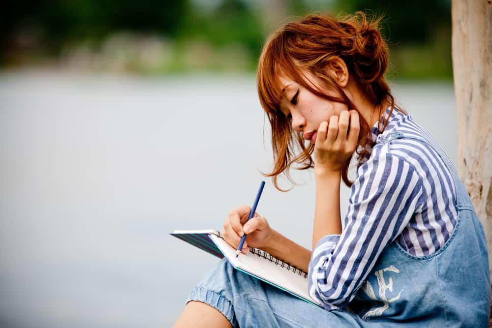 une fille est assise dehors en train d'écrire quelque chose