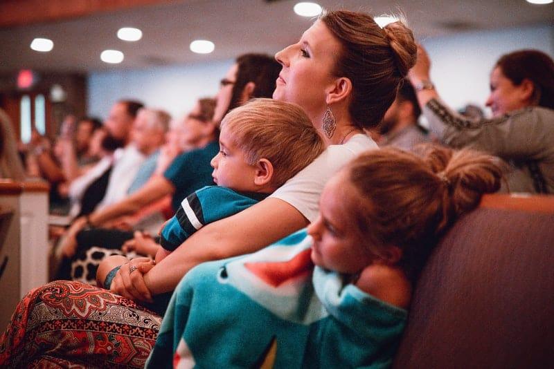 une mère avec deux enfants regarde un film au cinéma
