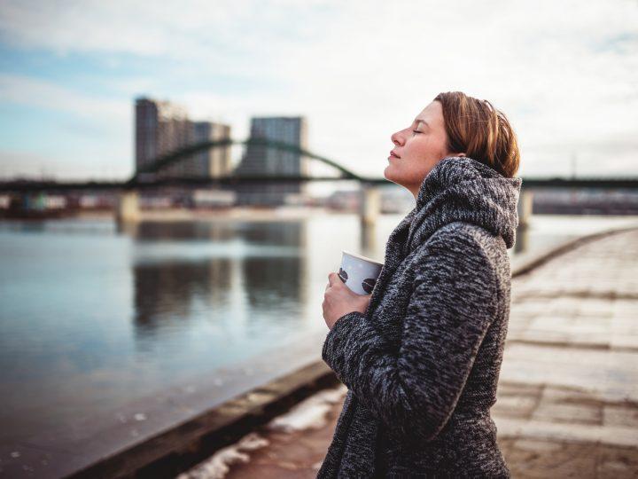 une femme se tient au bord de la rivière avec du café dans ses mains