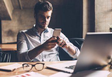 un homme est assis dans le bureau et les touches au téléphone