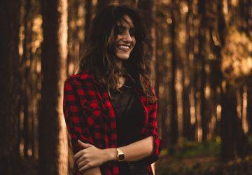 une femme debout dans une chemise à carreaux dans les bois