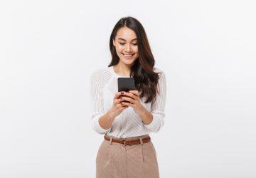 une femme debout avec un téléphone à la main