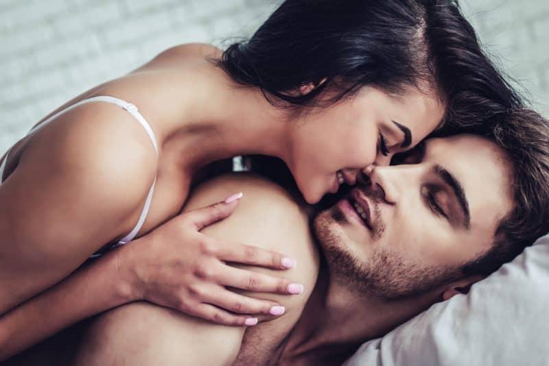 un homme et une femme à moitié nus au lit