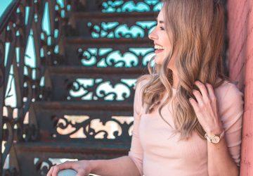 vue de côté d'une femme blonde souriante appuyée sur le mur