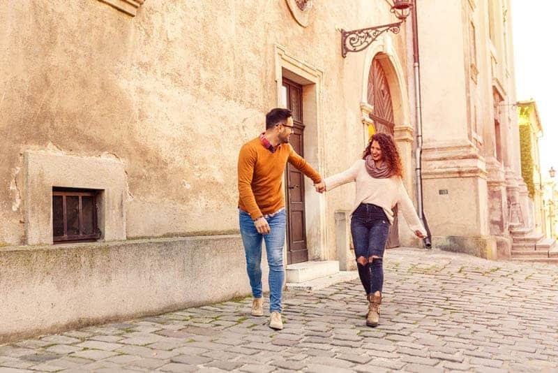 Un couple souriant se tenant par la main dans la rue