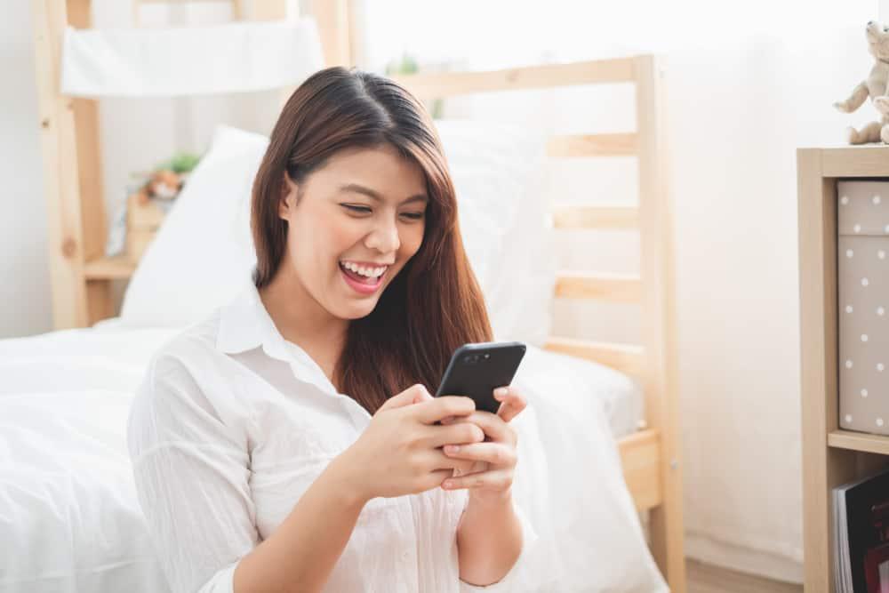 Une femme asiatique utilise un ordinateur portable et un smart phone