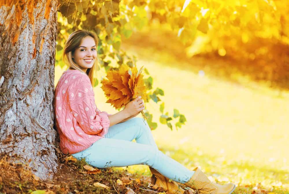 Une femme assise sur l'herbe à côté d'un arbre avec une feuille à la main