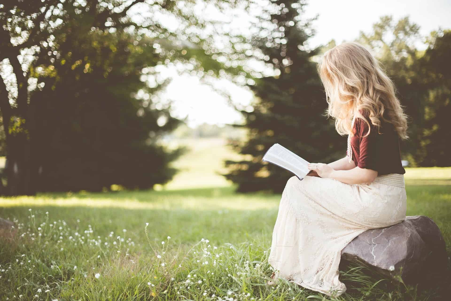 Une femme aux longs cheveux blonds est assise sur un rocher et lit un livre