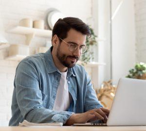 un homme est assis à une table et une clé sur un ordinateur portable