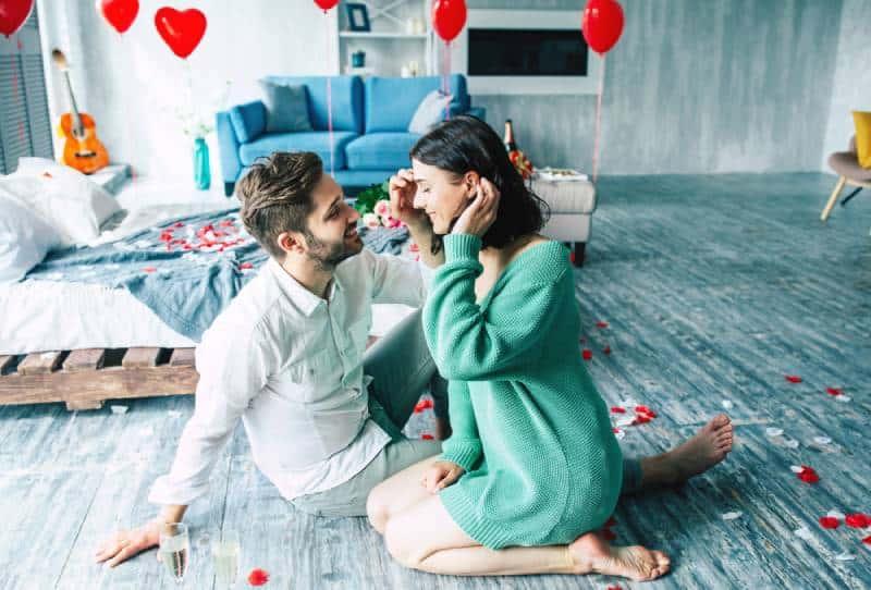 couple assis ensemble sur le sol dans une chambre romantique