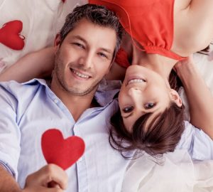 un homme et une femme heureux montrant un coeur rouge