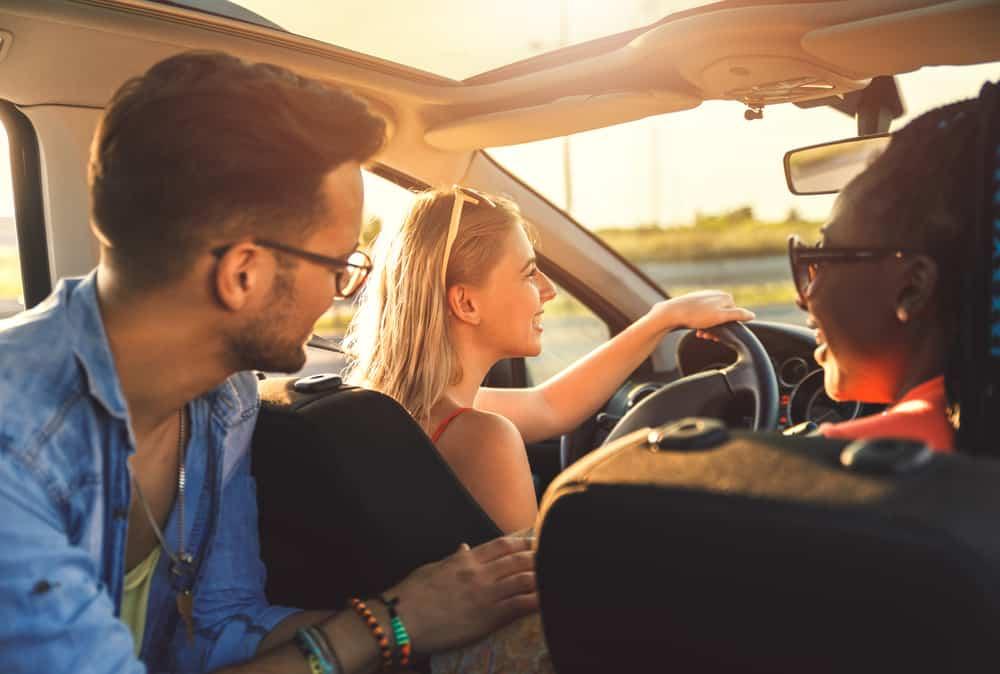 des amis montent dans la voiture et rient