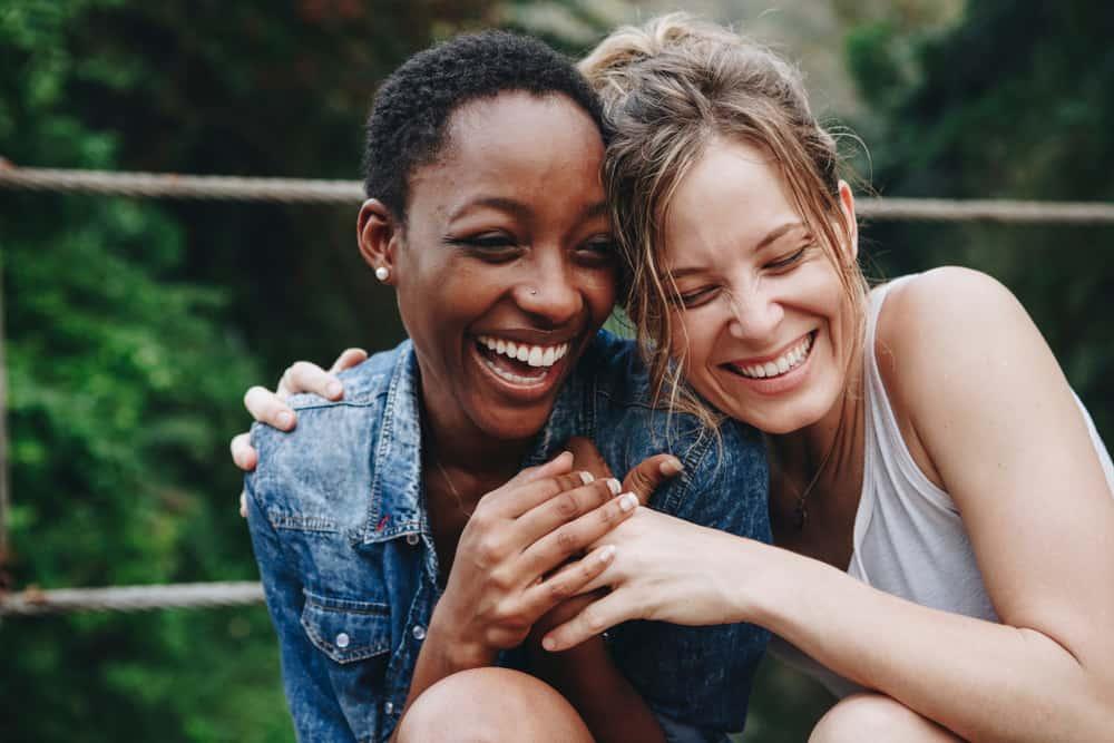 deux amis étreignant en riant