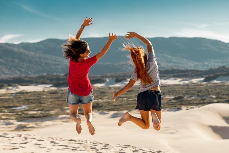 deux amis sautant sur le sable