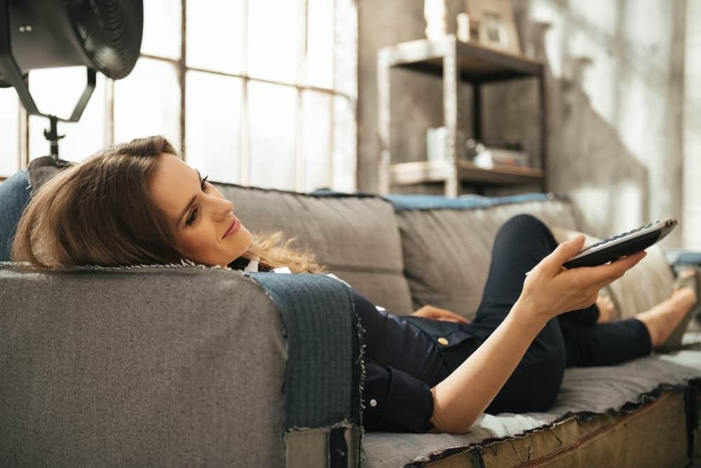 femme allongée sur le canapé et regarder la télé