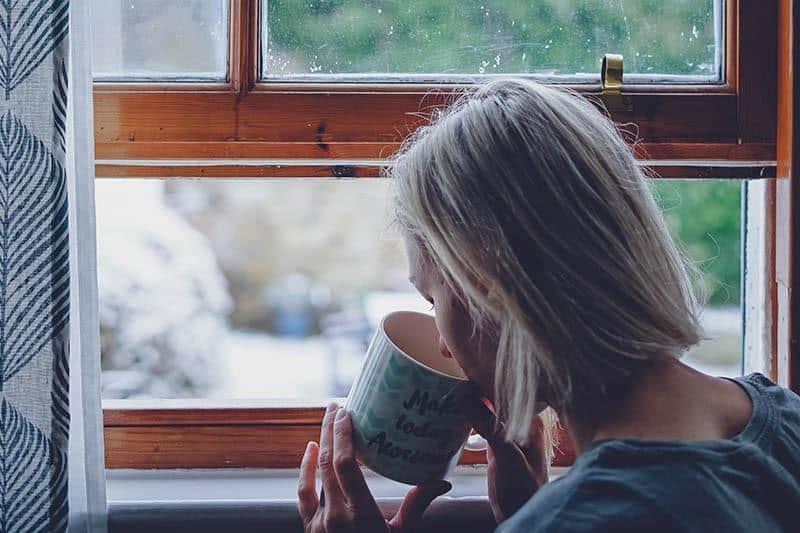 femme buvant un café près de la fenêtre