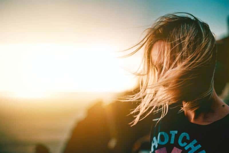 femme debout sur une colline au coucher du soleil