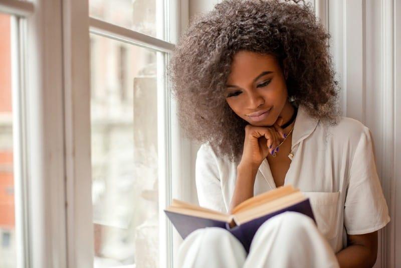 Jolie femme afro-américaine lisant un livre assis sur le rebord de la fenêtre