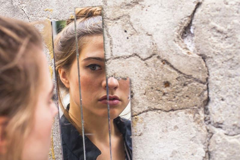 femme se regardant sur un miroir brisé