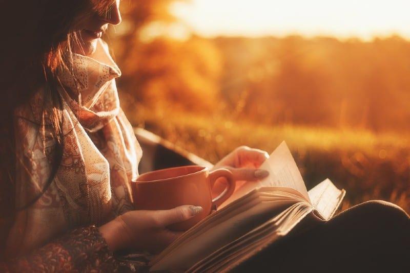 Belle fille dans la forêt d'automne en lisant un livre recouvert d'une couverture chaude