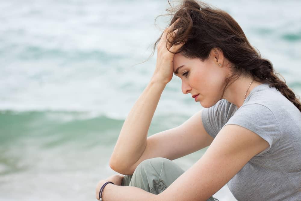 la femme est assise près de la plage et tient sa tête