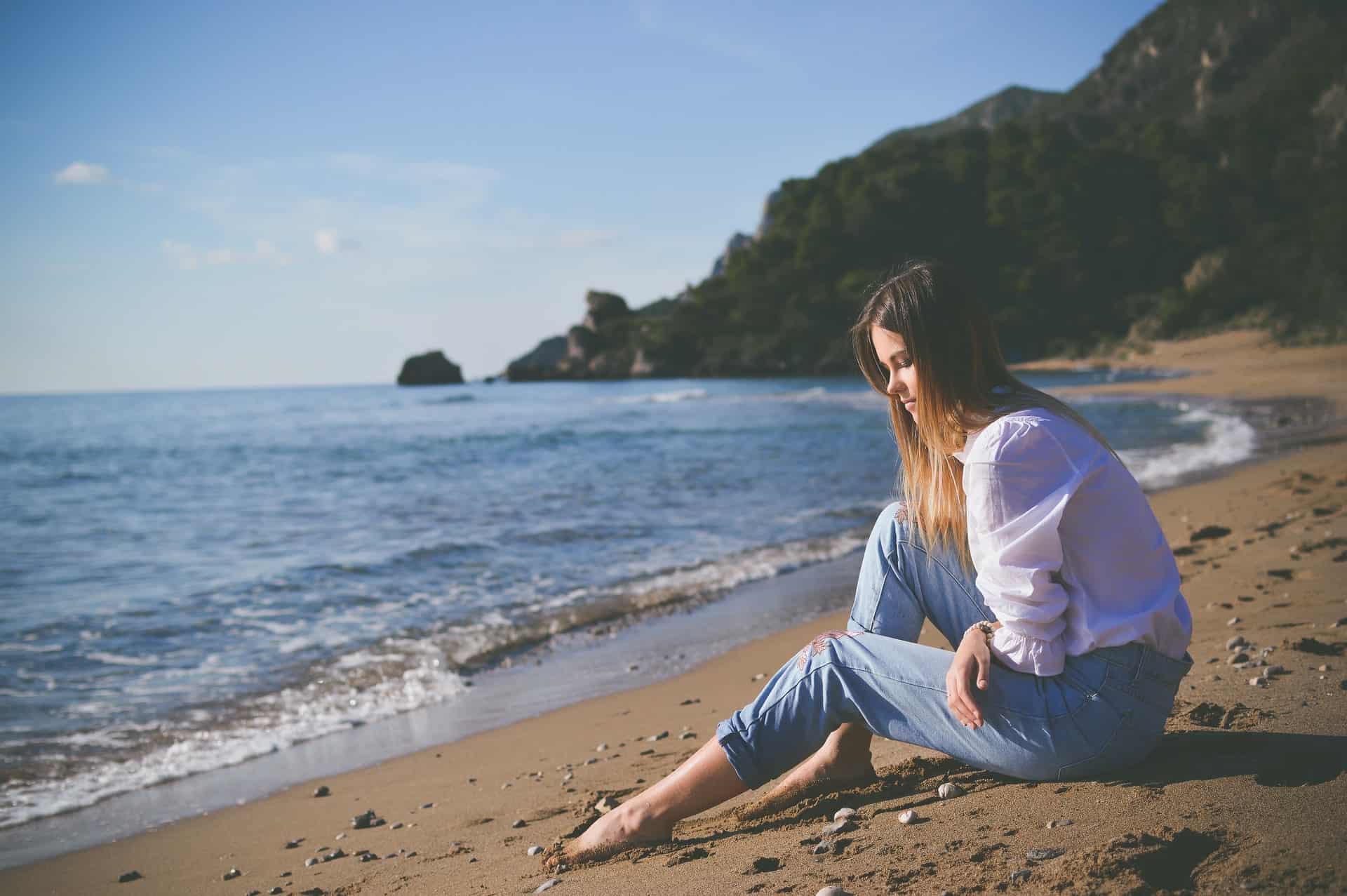 la femme est assise sur la plage et pense