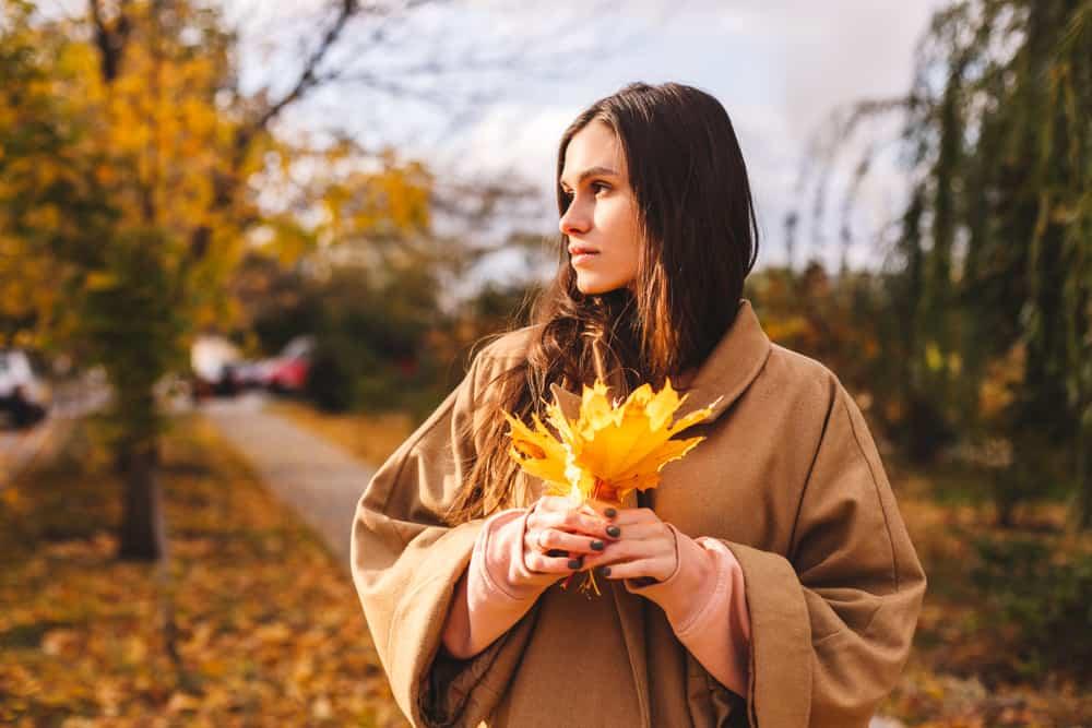 la femme tient les feuilles dans sa main et regarde ailleurs