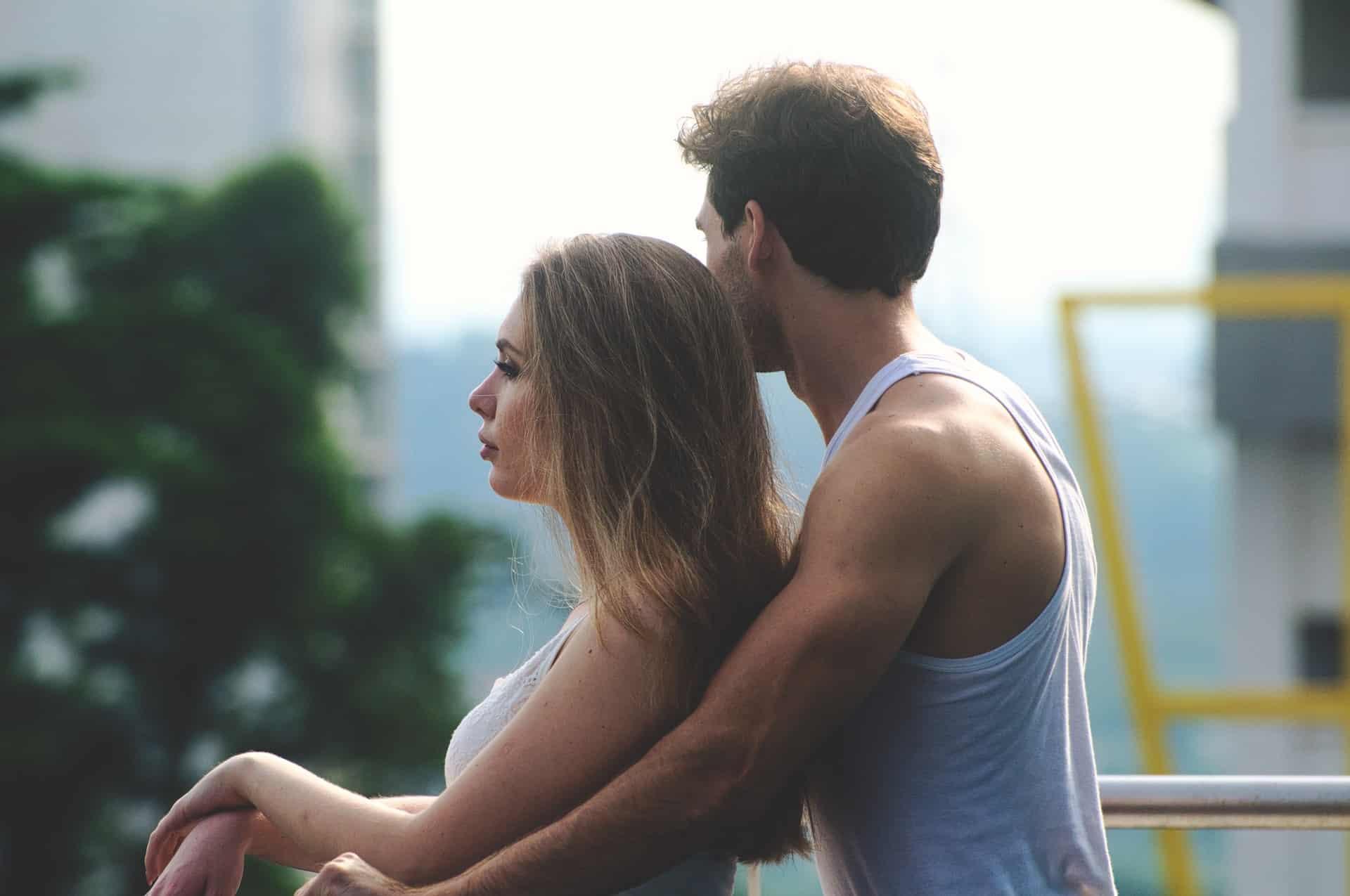 l'homme debout derrière la femme la serra dans ses bras