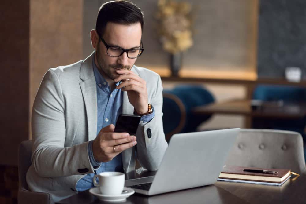 un homme assis à une table avec un bouton café sur le téléphone