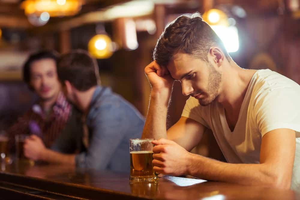 un homme est assis derrière un traîneau et boit une bière