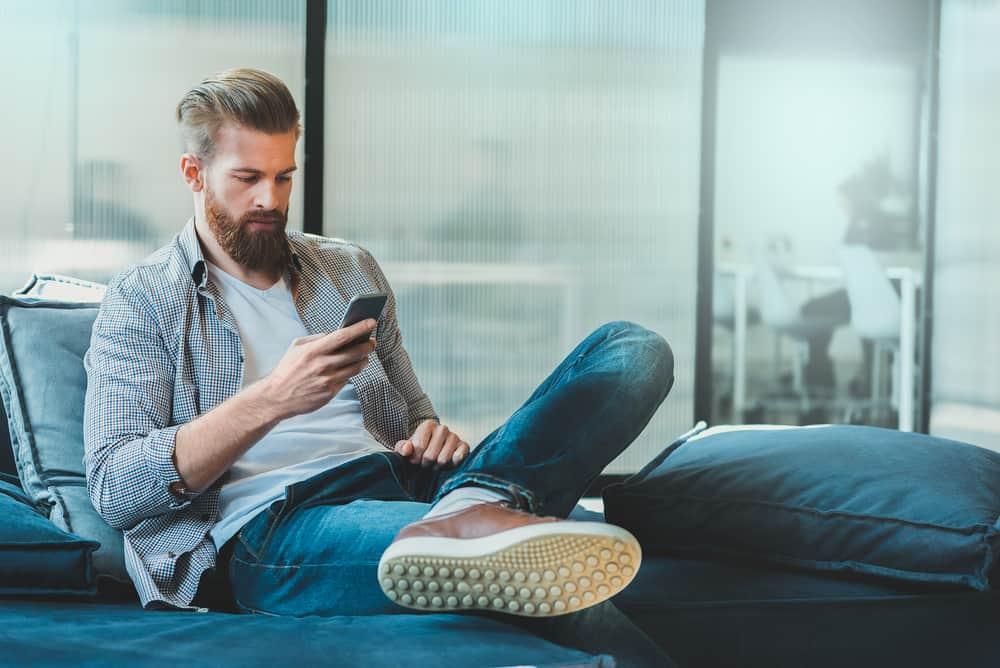 un homme est assis sur le canapé et un bouton sur le téléphone