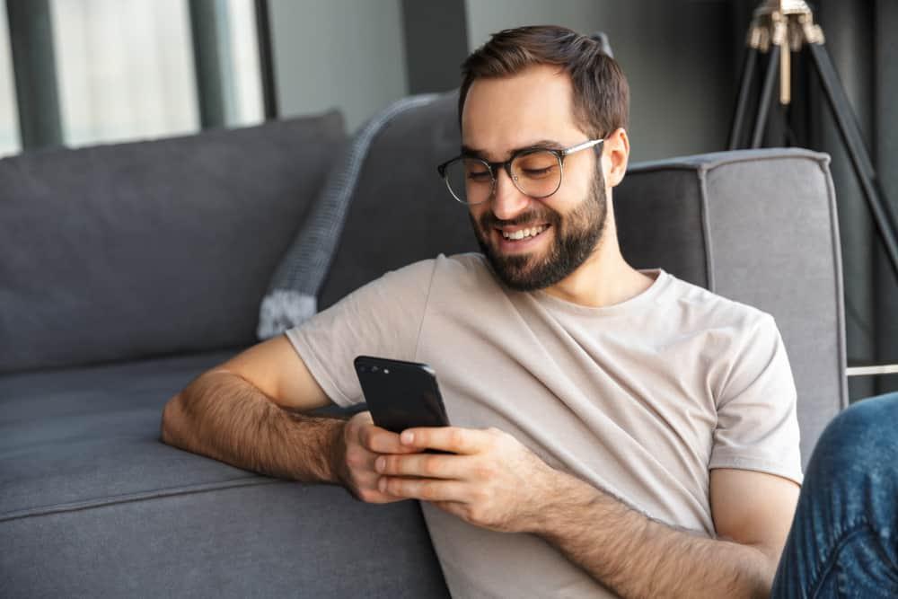 un homme est assis sur le sol et un bouton sur le téléphone