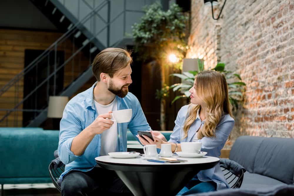 un homme et une femme assis à une table à parler et à boire du café
