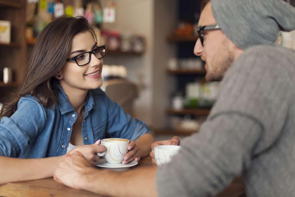 un homme et une femme parlant autour du café