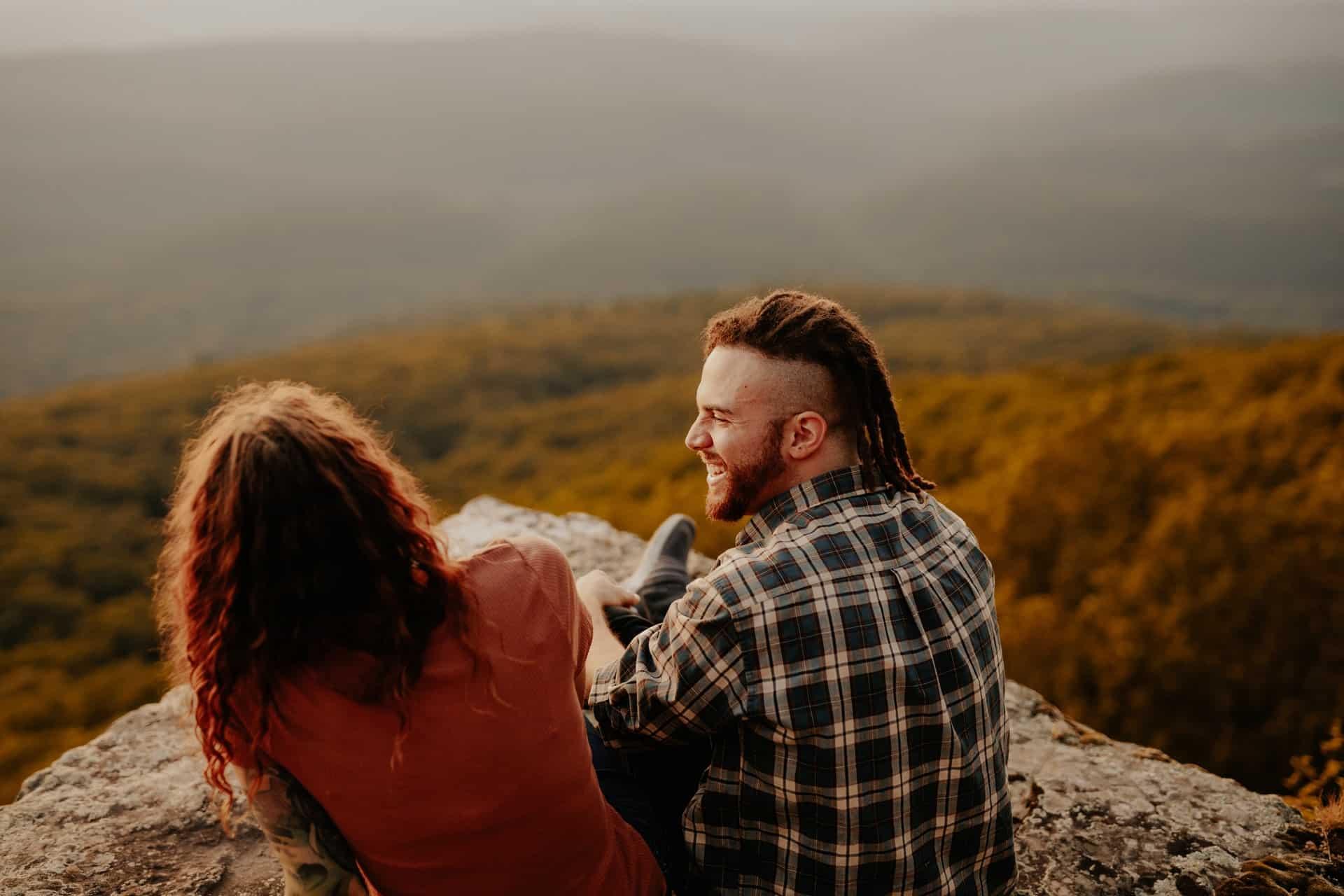 un homme et une femme s'assoient sur un rocher et rient